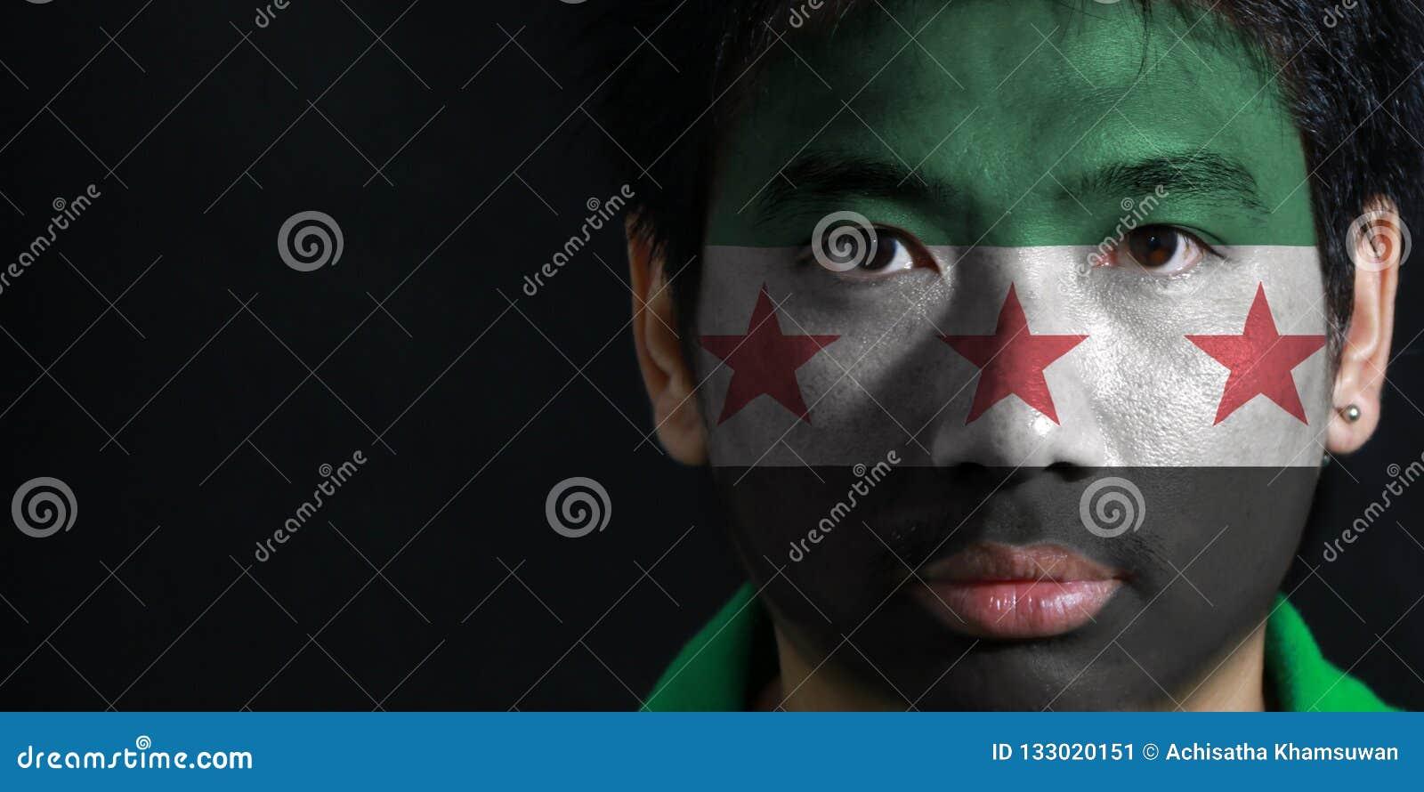 Ståenden av en man med flaggan av den syrianska provisoriska regeringen målade på hans framsida på svart bakgrund