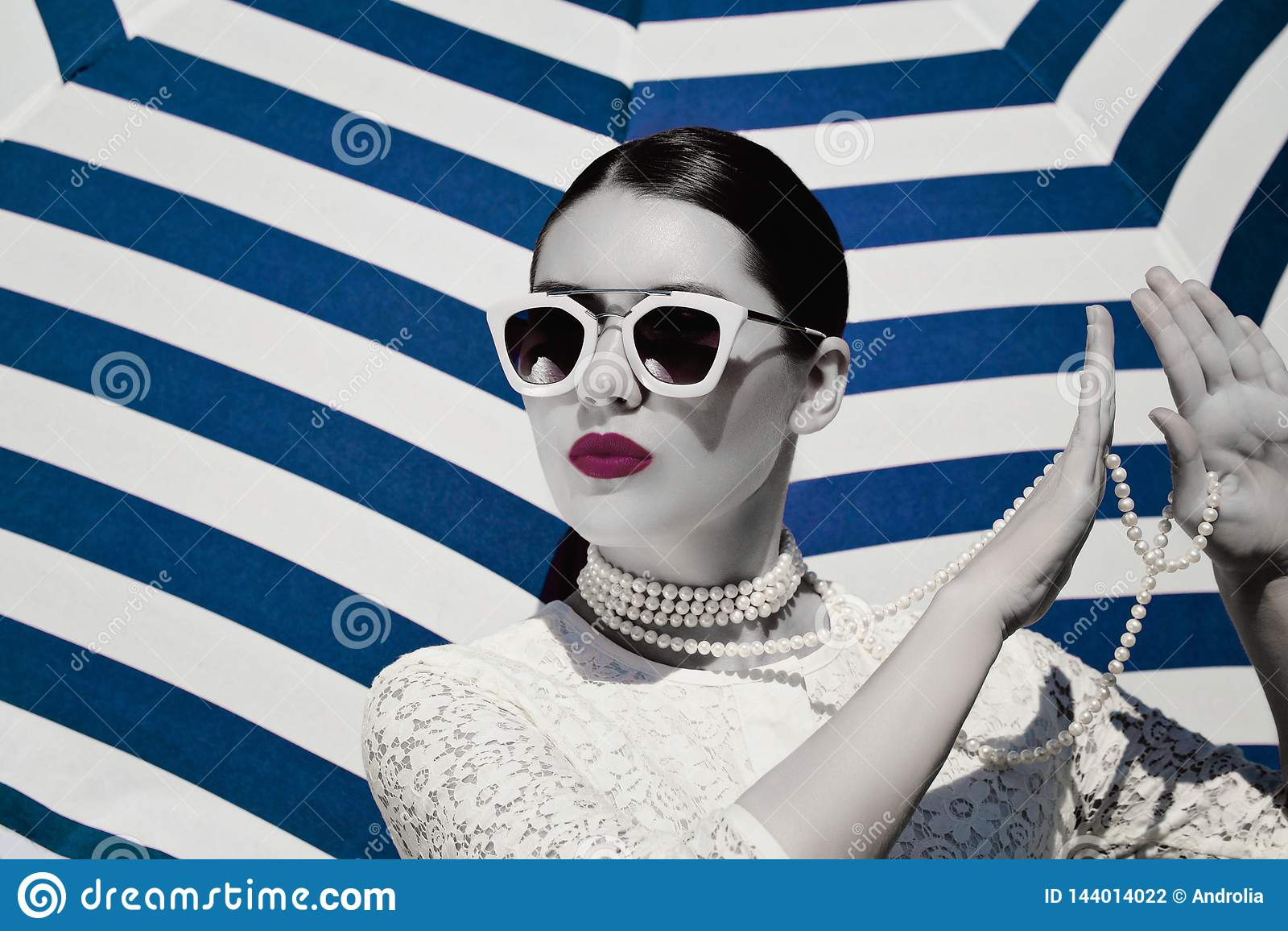 Ståenden av en nätt ung kvinna i vit snör åt klänningen, den vit pärlemorfärg halsbandet och ljust - rosa solglasögon