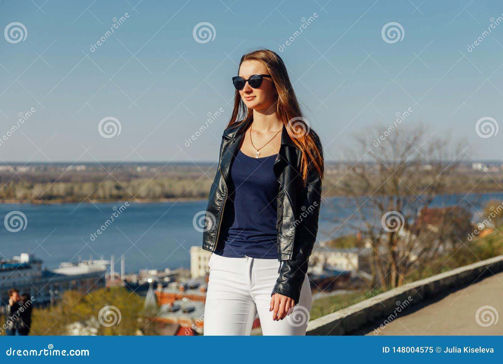 Ståenden av en stilfull mörker-haired flicka i solglasögon, är hon i ett läderomslag