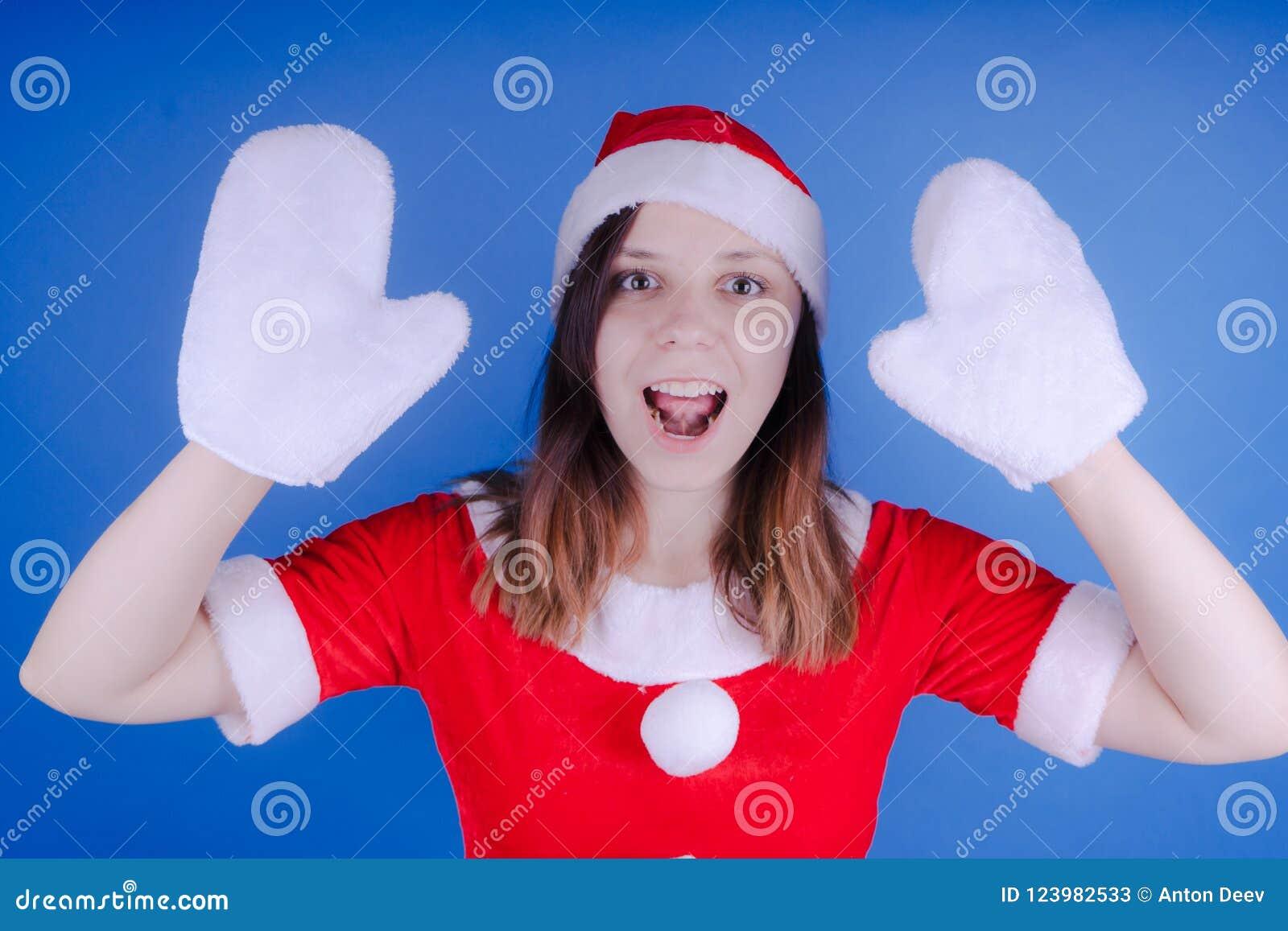 Ståenden av en ung flicka klädde som Santa Claus på en blå bakgrund Lyckligt nytt år och glad jul!