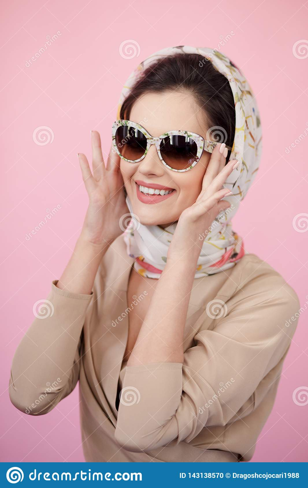 Ståenden av en ung kvinna som bär elegant kläder, solglasögon, trycker på han hans exponeringsglas med hans händer, rosa bakgrund