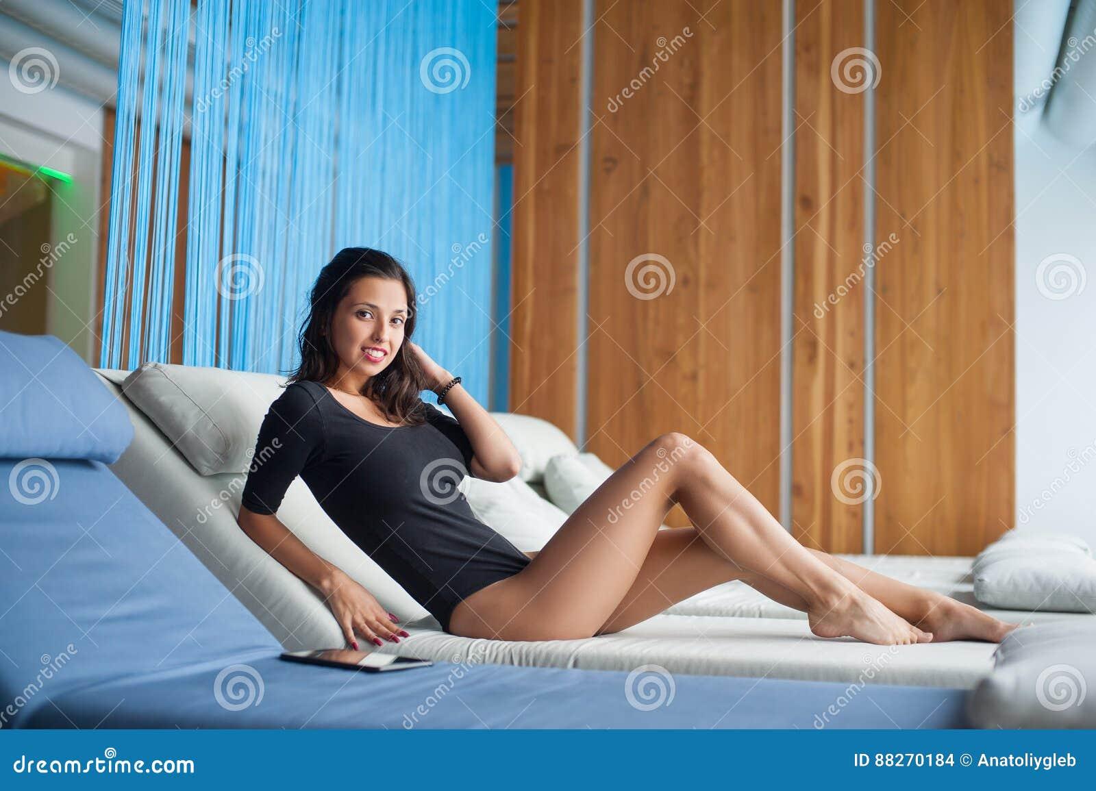 Ståenden av kvinnlign med perfekt hud i svart bodysuit ligger på den vita dagdrivaren på vardagsrumzonen i brunnsortsemesterorten