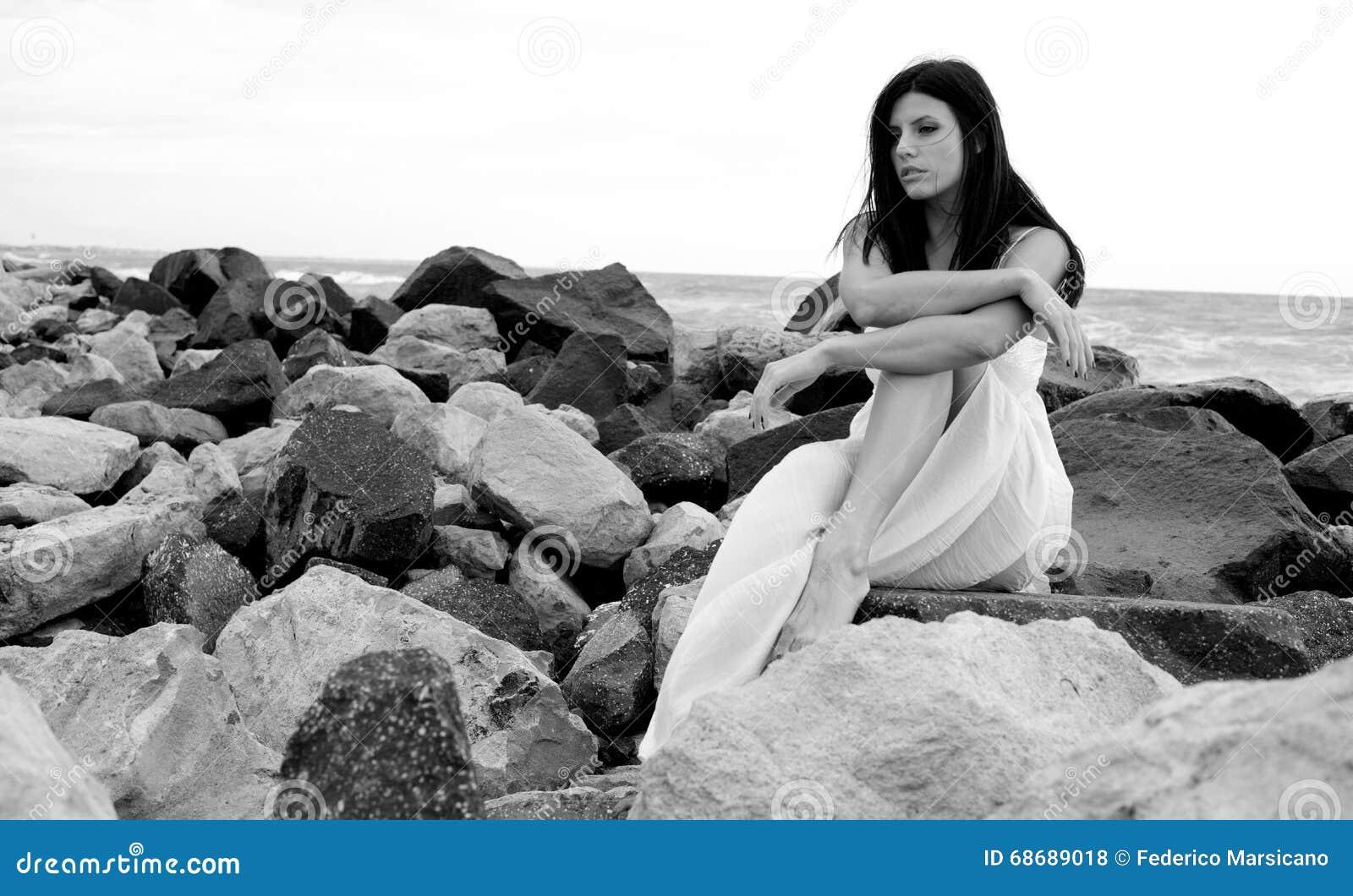 Ståenden av ledset kvinnasammanträde vaggar på framme av havet