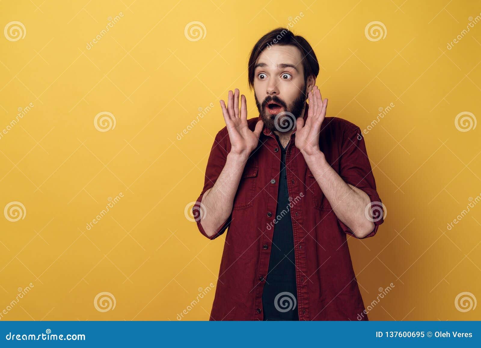 Ståenden av Shocked den skäggiga mannen håller upp händer