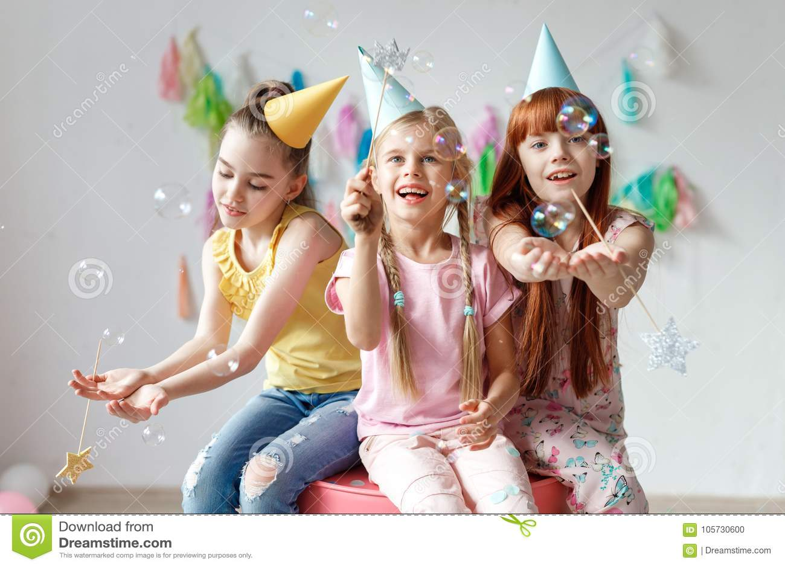 Ståenden av tre härliga flickor bär festliga lock, spelar med bubblor, sitter tillsammans på stol, firar födelsedag och att vara