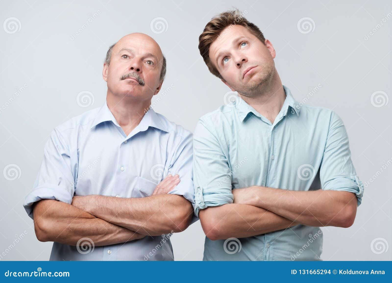 Ståenden av två män med borrat matat upp uttryckt, blickar misshog upp, tröttas för att förklara deras fruar var de var