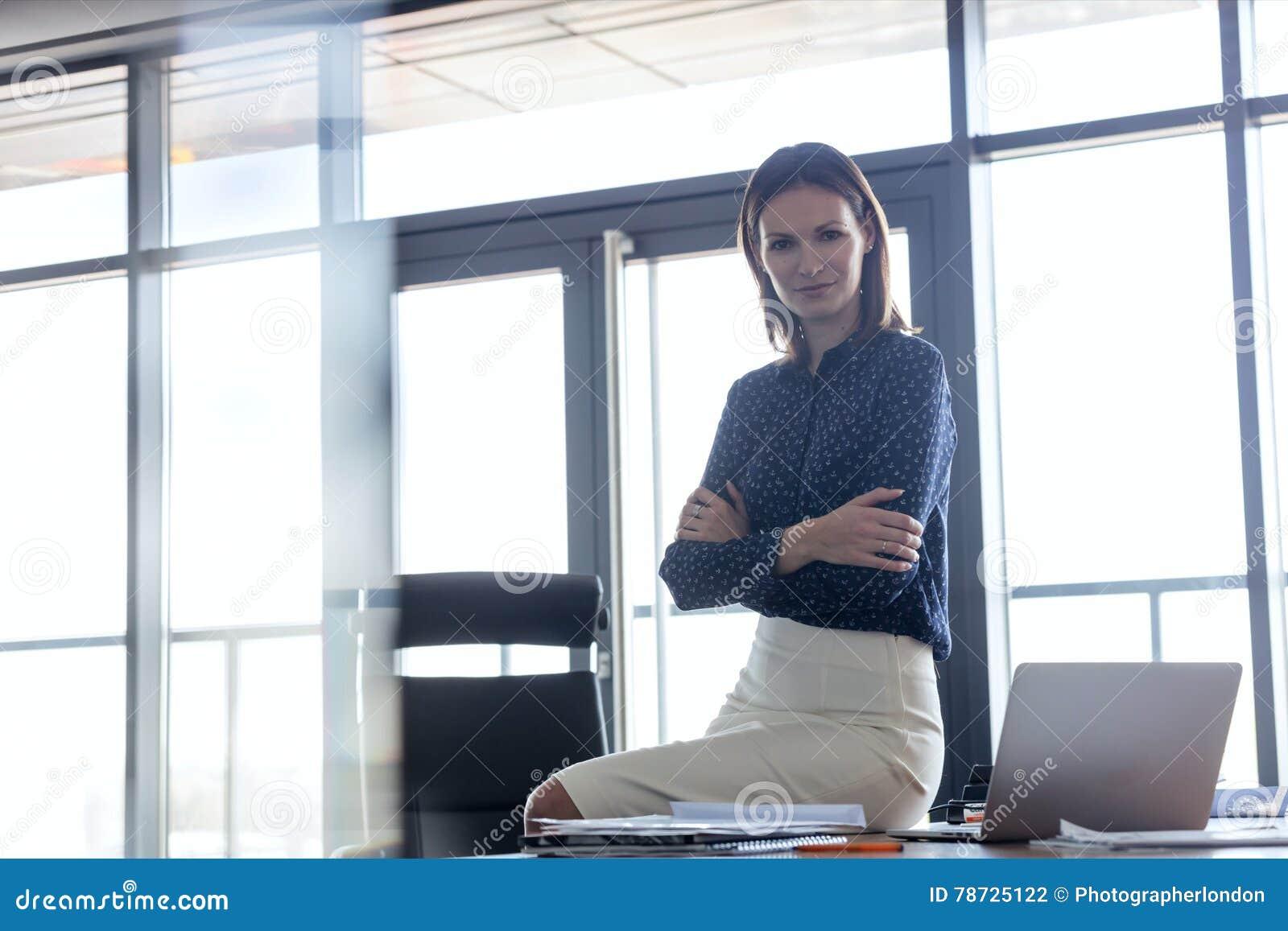 Ståenden av unga affärskvinnasammanträdearmar korsade på skrivbordet i regeringsställning