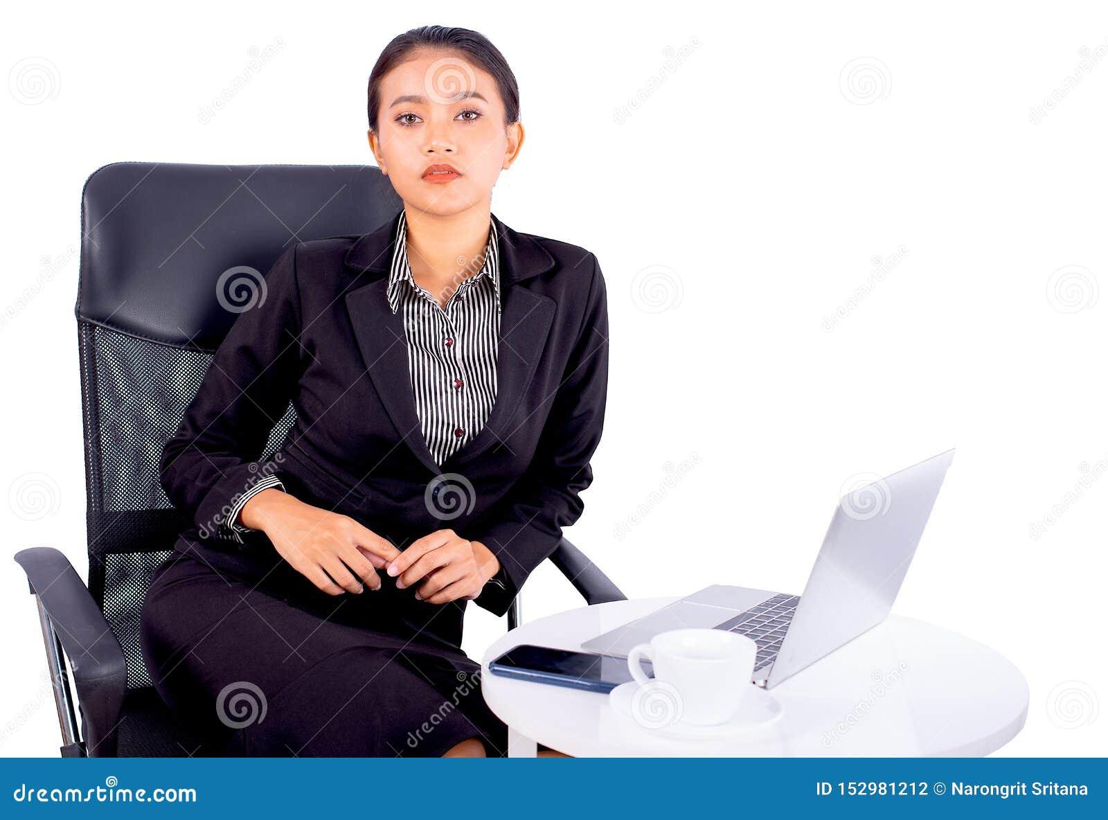 Ståenden isolerade sydostliga asiatiska affärskvinnan bär mörkt - den gråa dräkten ser kameran och sitter på stol med kontoret