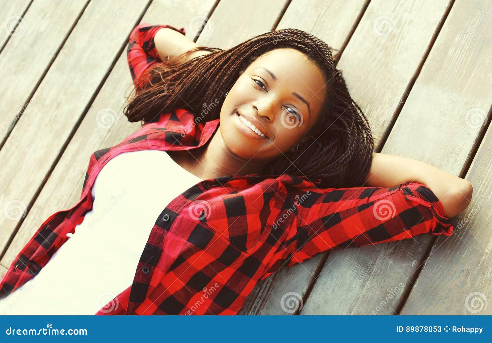 Ståenden som ler den unga afrikanska kvinnan, kopplade av på ett trägolv med händer bak huvudet som bär en röd rutig skjorta