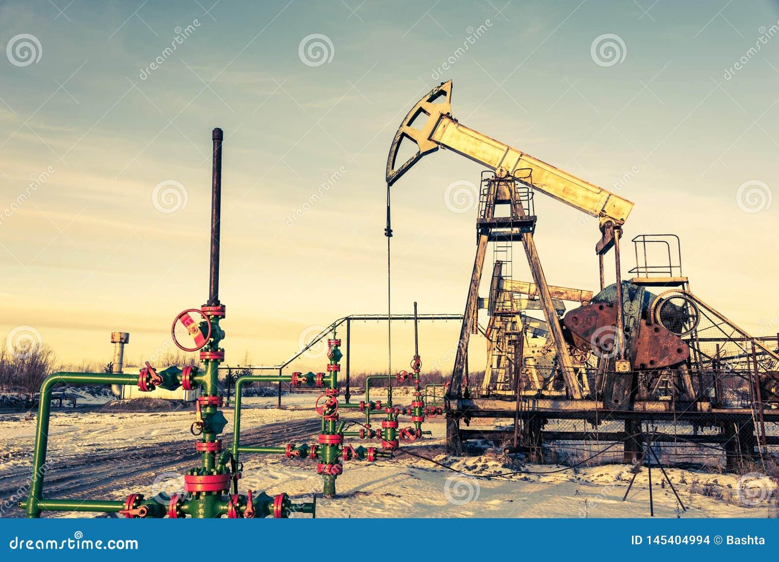 St?lar och wellhead f?r oljapump p? en oljef?lt Bryta och oljabransch Kraftgenereringbegrepp
