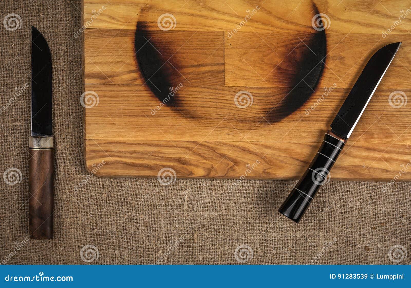 Stålkökkniv på ett träbräde