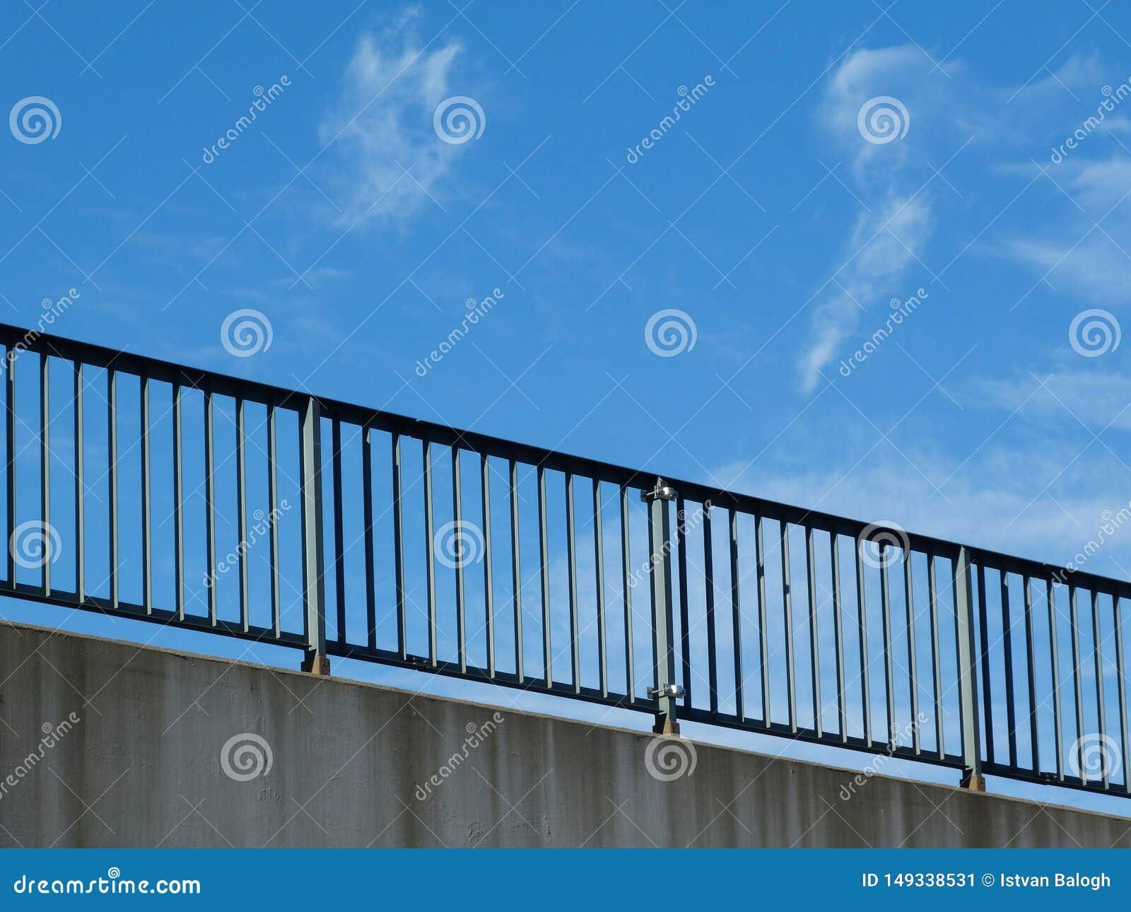Stålvaktstång med posteringar och stolpar på huvudvägen med blå himmel
