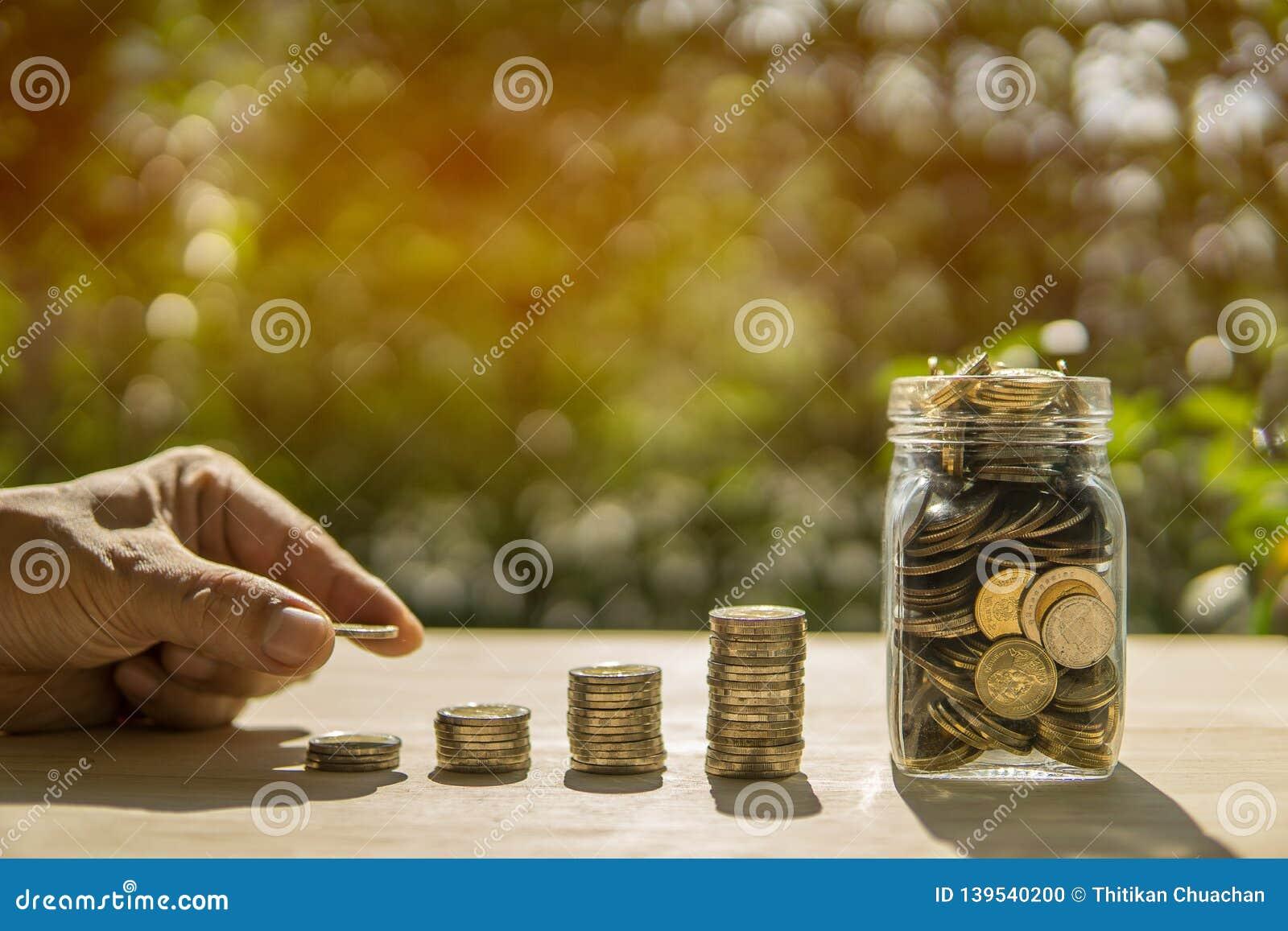 Stången och kruset för manhandmynt på trätabellen i solljus- och suddighetsbakgrund framlägger besparingarna myntar - investering