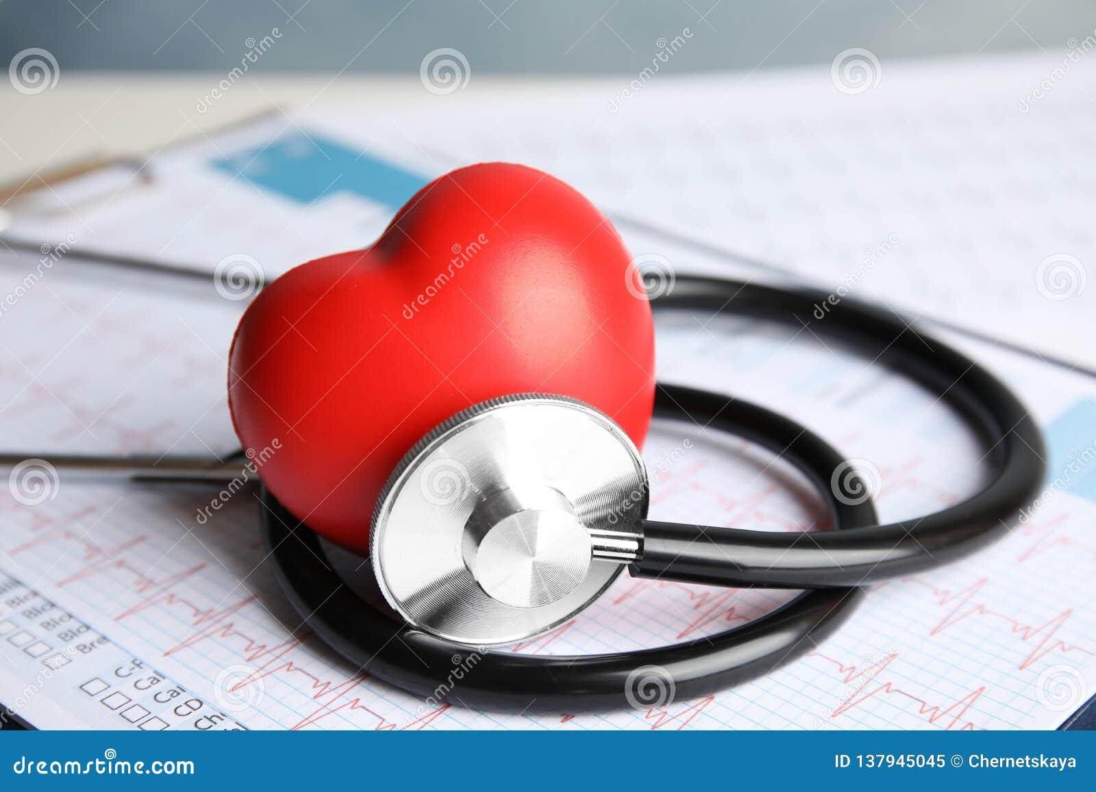 Stéthoscope, coeur rouge et cardiogramme sur la table