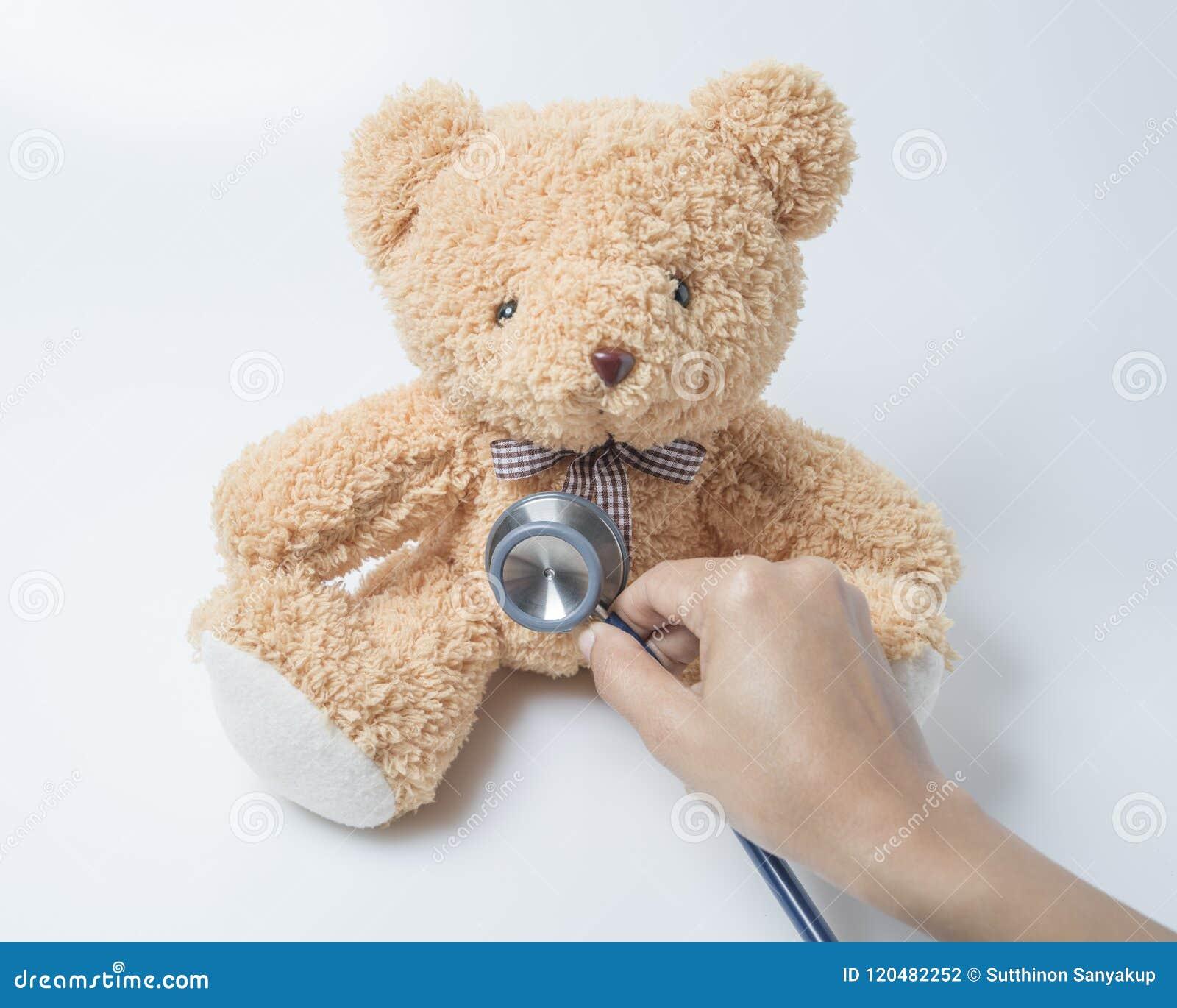 Stéthoscope de coeur d ours de nounours de soins de santé sur le fond blanc