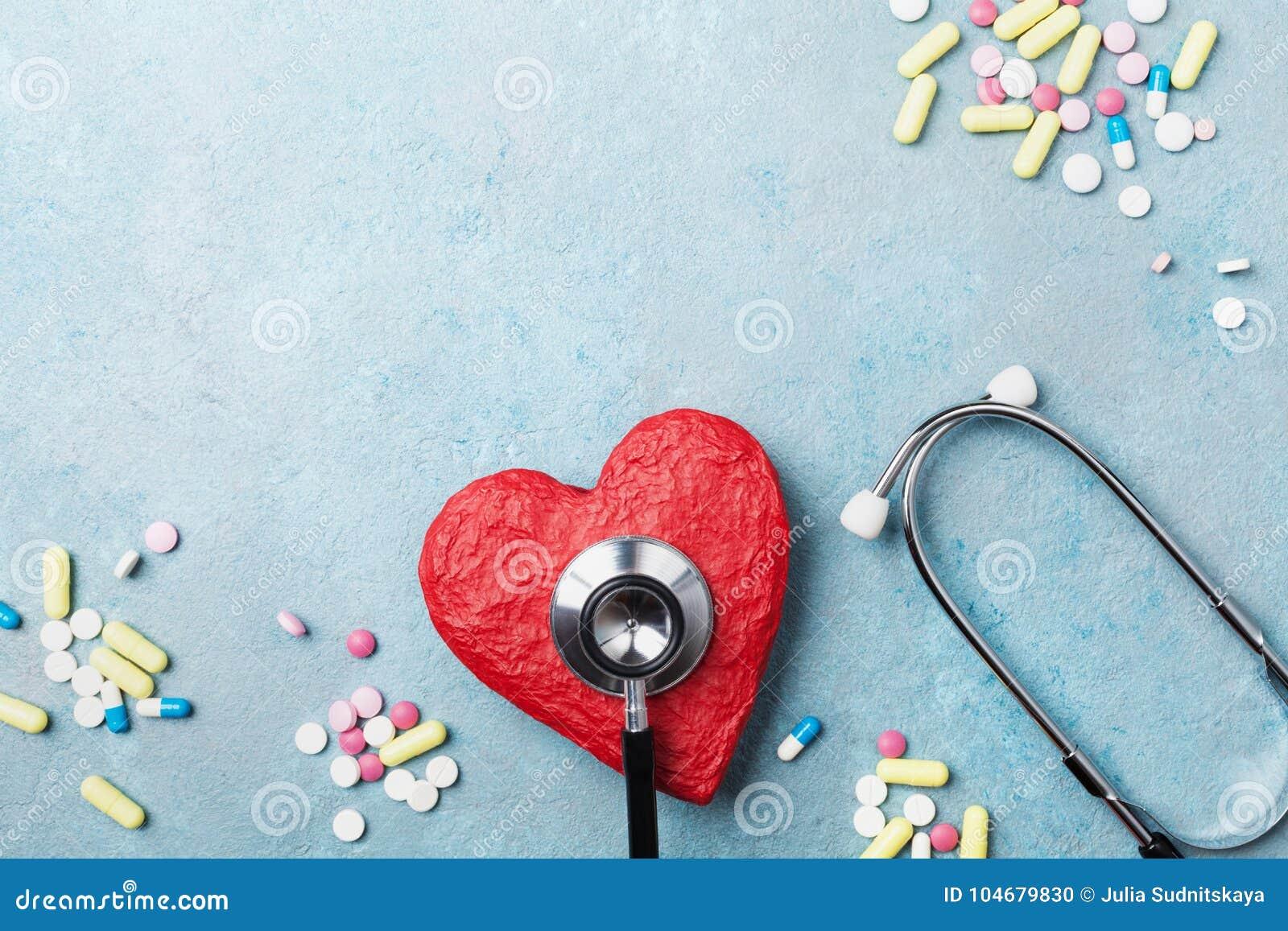 Stéthoscope médical, coeur rouge et pilules de drogue sur la vue supérieure de fond bleu Concept saine et de tension artérielle