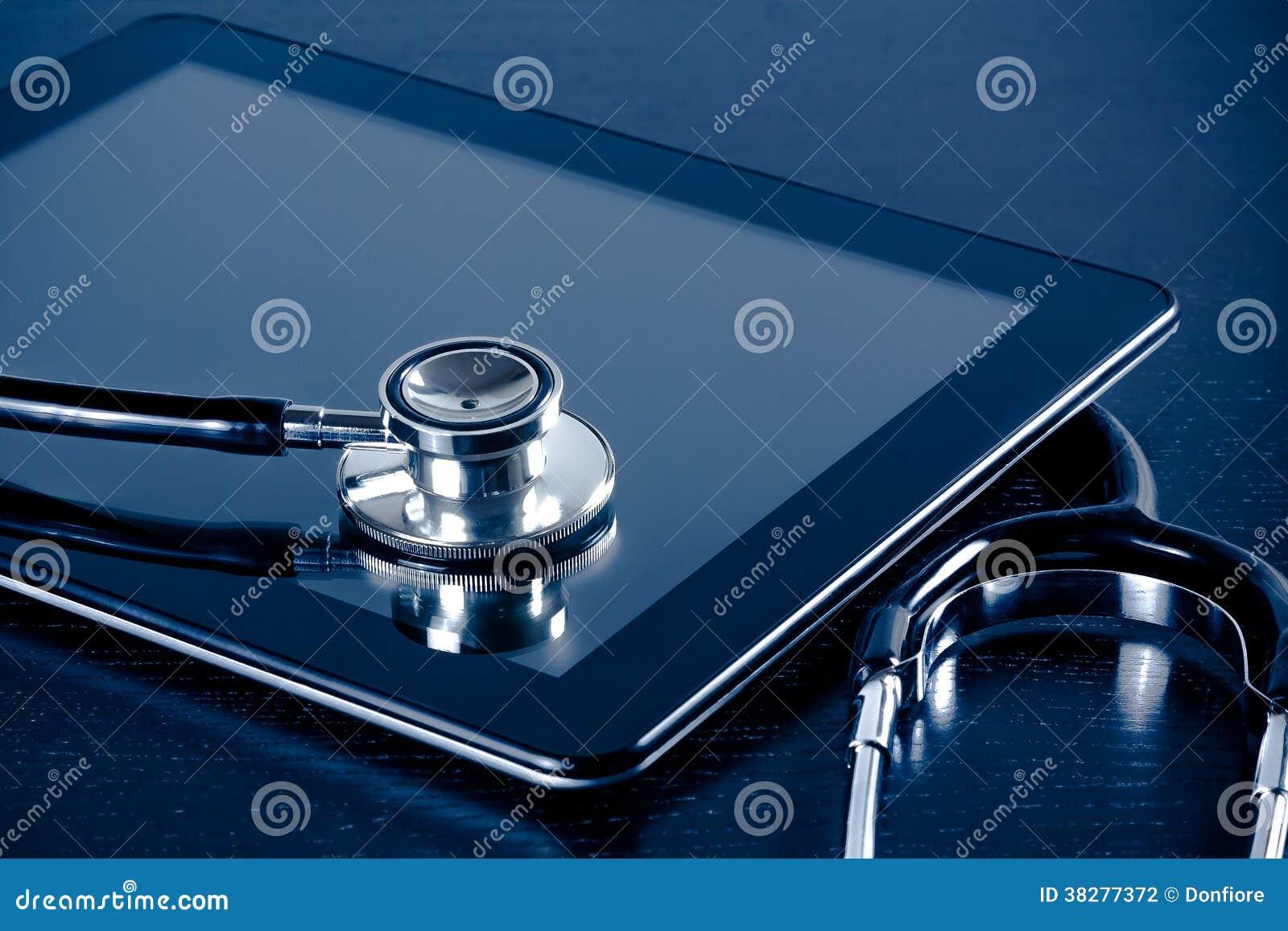 Stéthoscope médical sur le PC numérique moderne de comprimé dans le laboratoire sur la table en bois