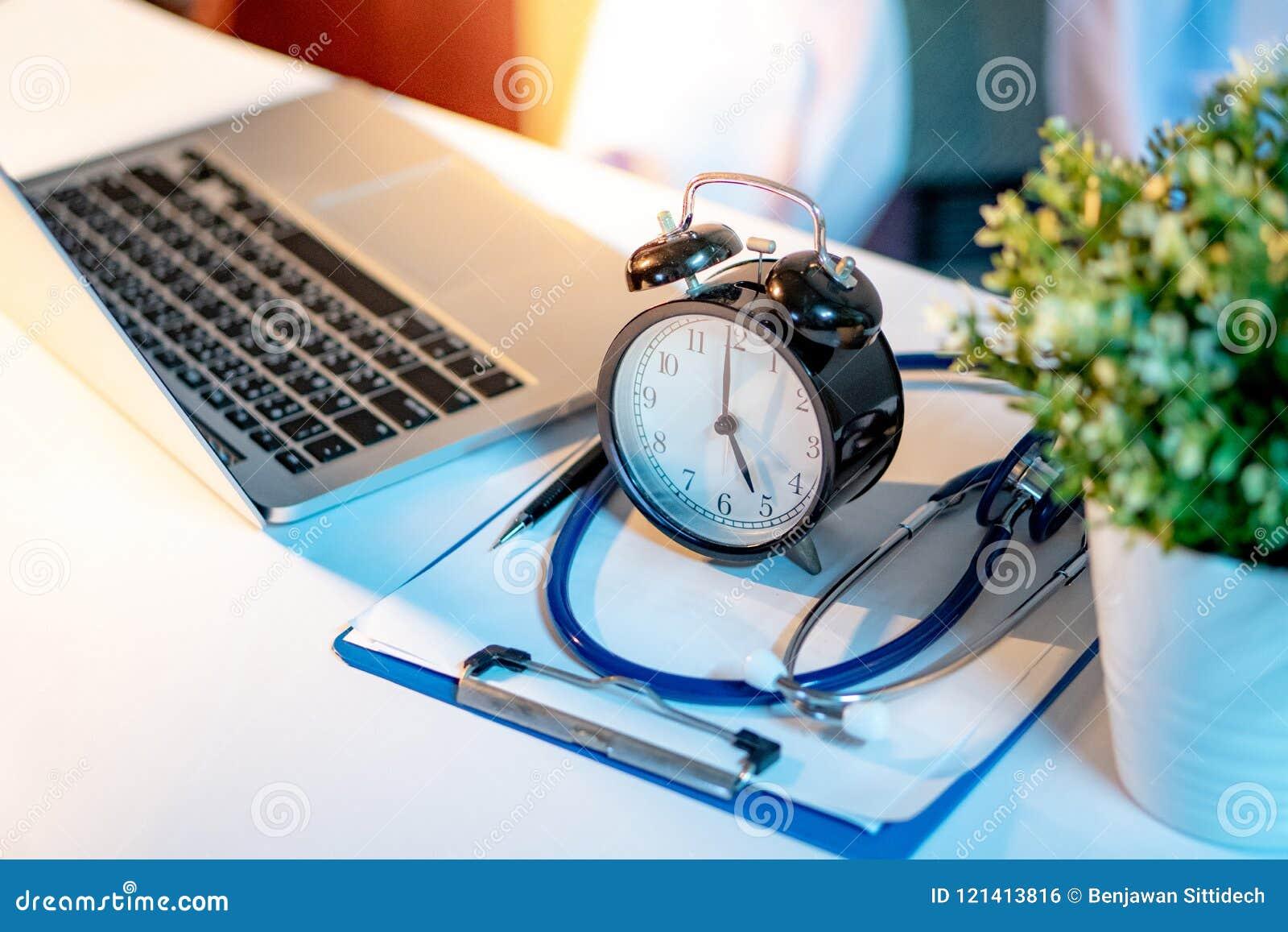 Stéthoscope, presse-papiers, horloge et ordinateur portable sur le bureau de docteur