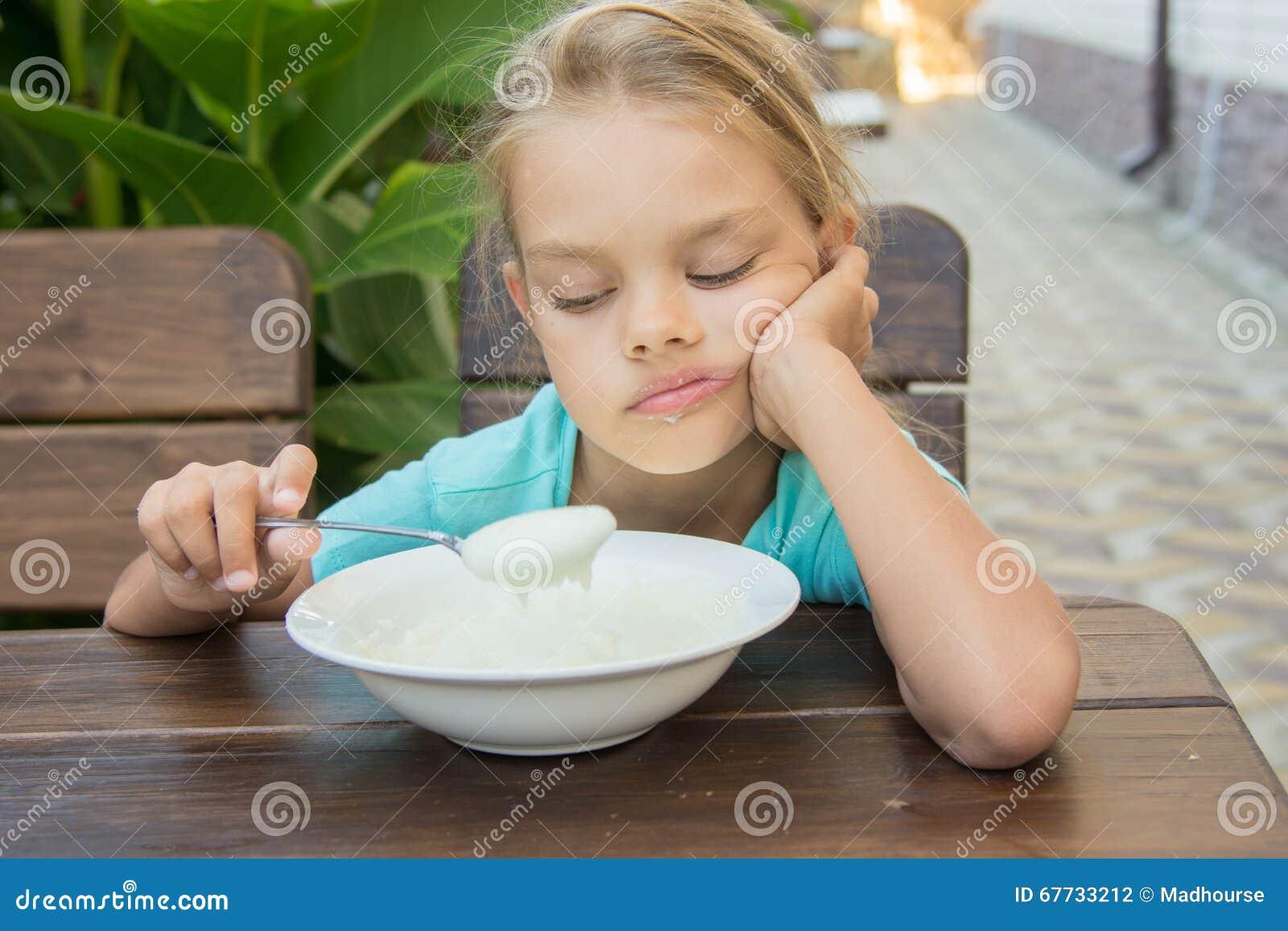 Stören Sie sechs Jährigmädchen, das traurig dem Grieß in einem Löffel auf Frühstück betrachtet