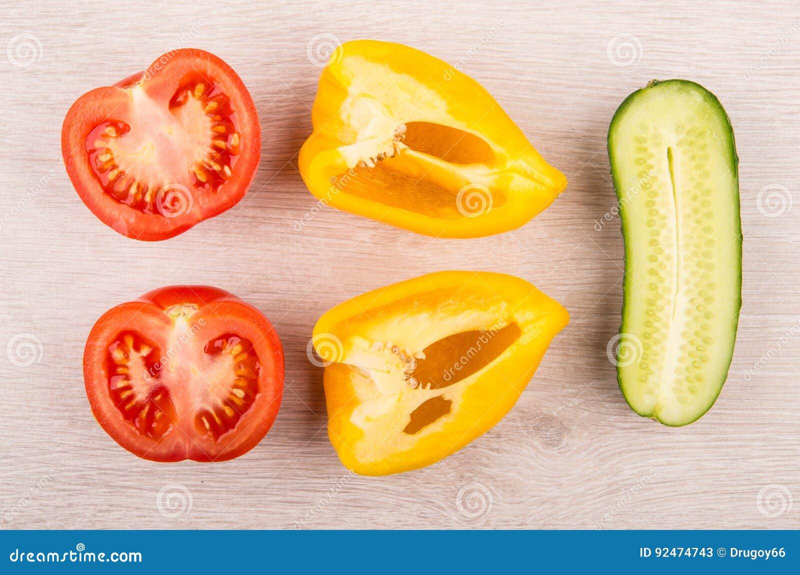 Stücke der Tomate, des Gemüsepaprikas und der Gurke auf Holztisch
