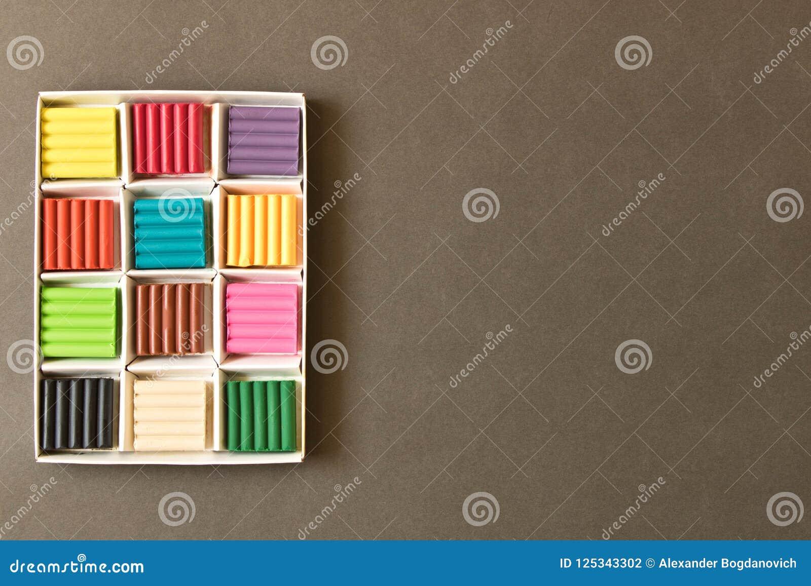 Stücke Kind-` s Lehm auf dem Hintergrund der Tafel T