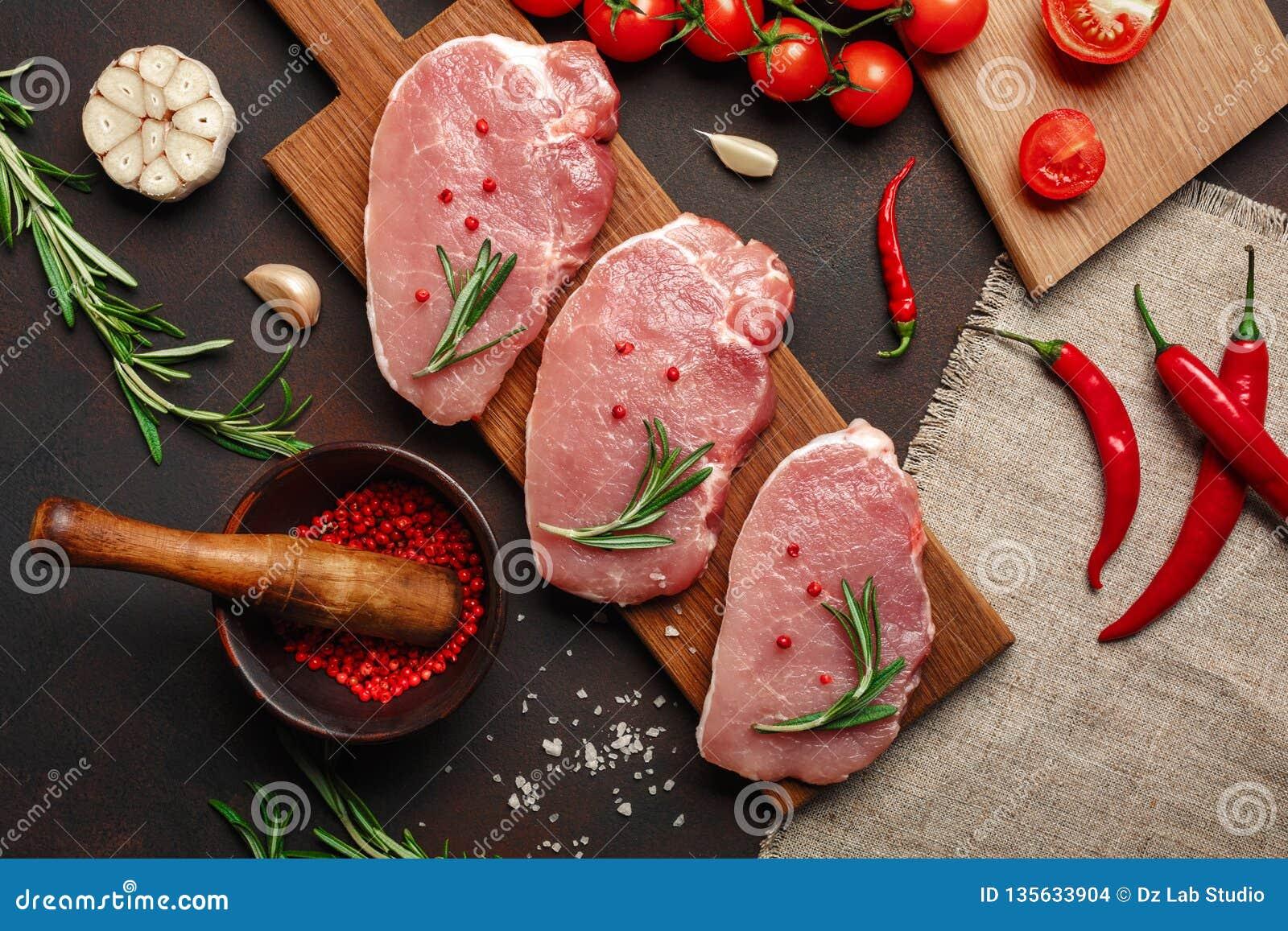 Stücke rohes Schweinefleischsteak auf Schneidebrett mit Kirschtomaten-, Rosmarin-, Knoblauch-, Pfeffer-, Salz- und Gewürzmörser a