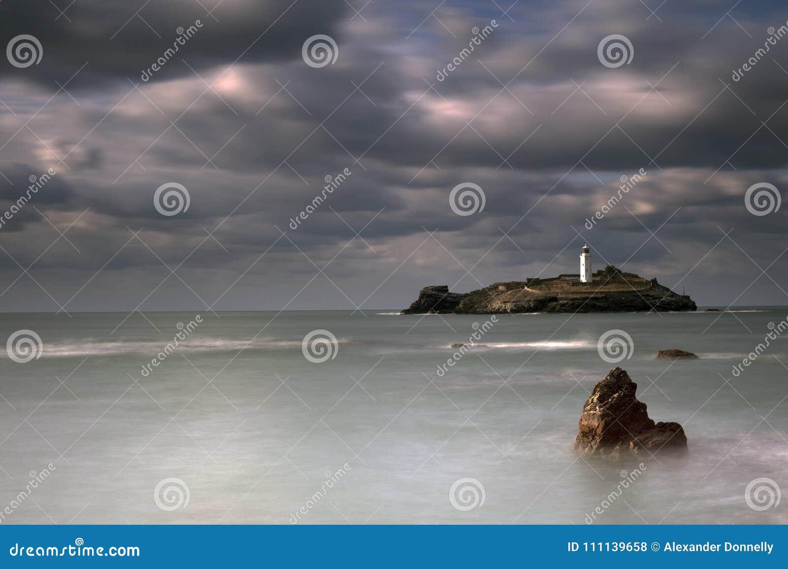 Stürmische Himmel über Godrevy-Leuchtturm auf Godrevy-Insel in St. Ives Bay mit dem Strand und Felsen im Vordergrund, Cornwall Gr