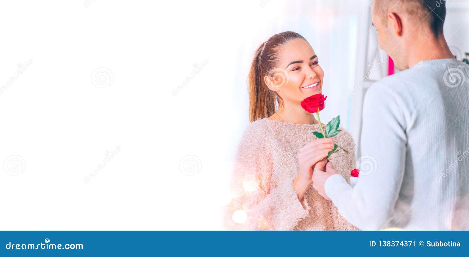 St Dag för valentin` s man för begreppskyssförälskelse till kvinnan Ung man som ger en blomma till hans flickvän