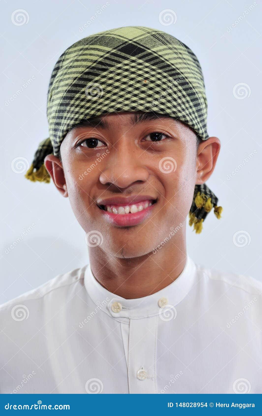 St?ende av att le den asiatiska muslim mannen som v?lkomnar dig