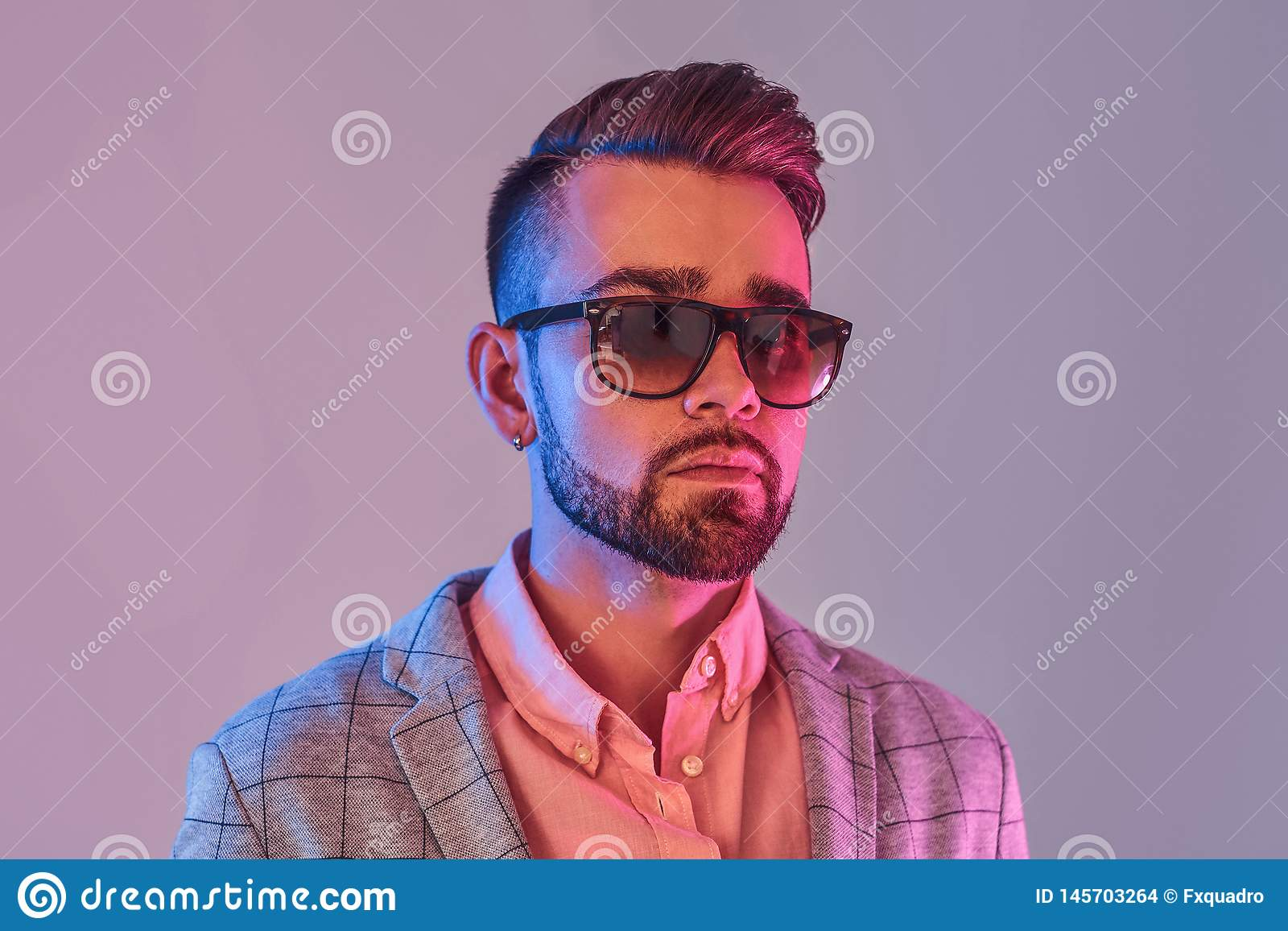 St?ende av den attraktiva eftert?nksamma mannen i checkeretblazer och solglas?gon