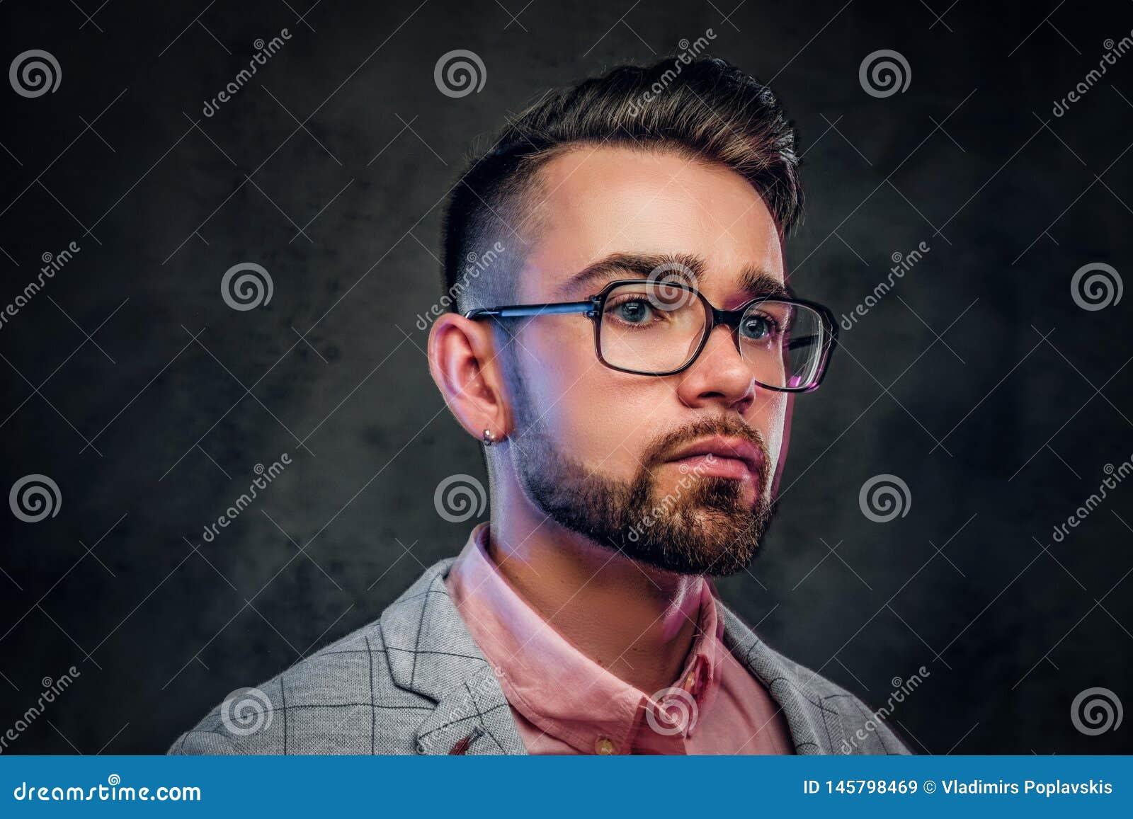 St?ende av den attraktiva eftert?nksamma mannen i rutig blazer, rosa skjorta och exponeringsglas
