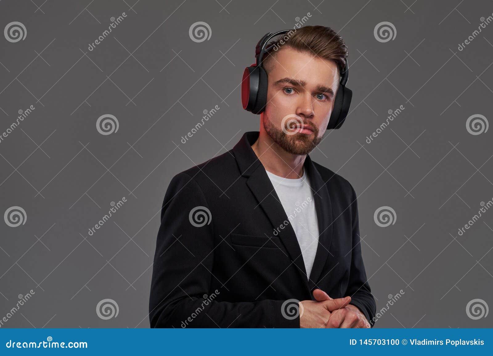 St?ende av den attraktiva unga mannen i tr?dl?s h?rlurar som ?r lyssnande musik