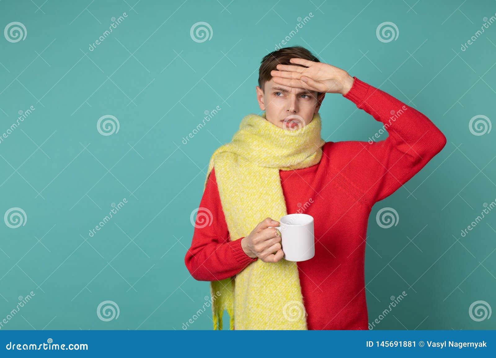 St?ende av den gladlynta ledsna d?ligt unga mannen i r?d sweeater och den gula halsduken med koppen av varmt te