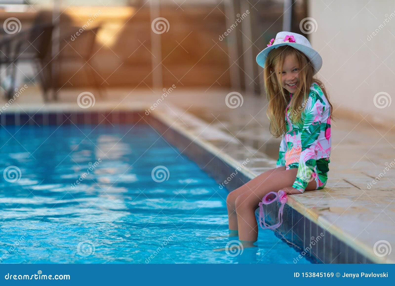 St?ende av den gulliga lyckliga lilla flickan som har gyckel i simbass?ng