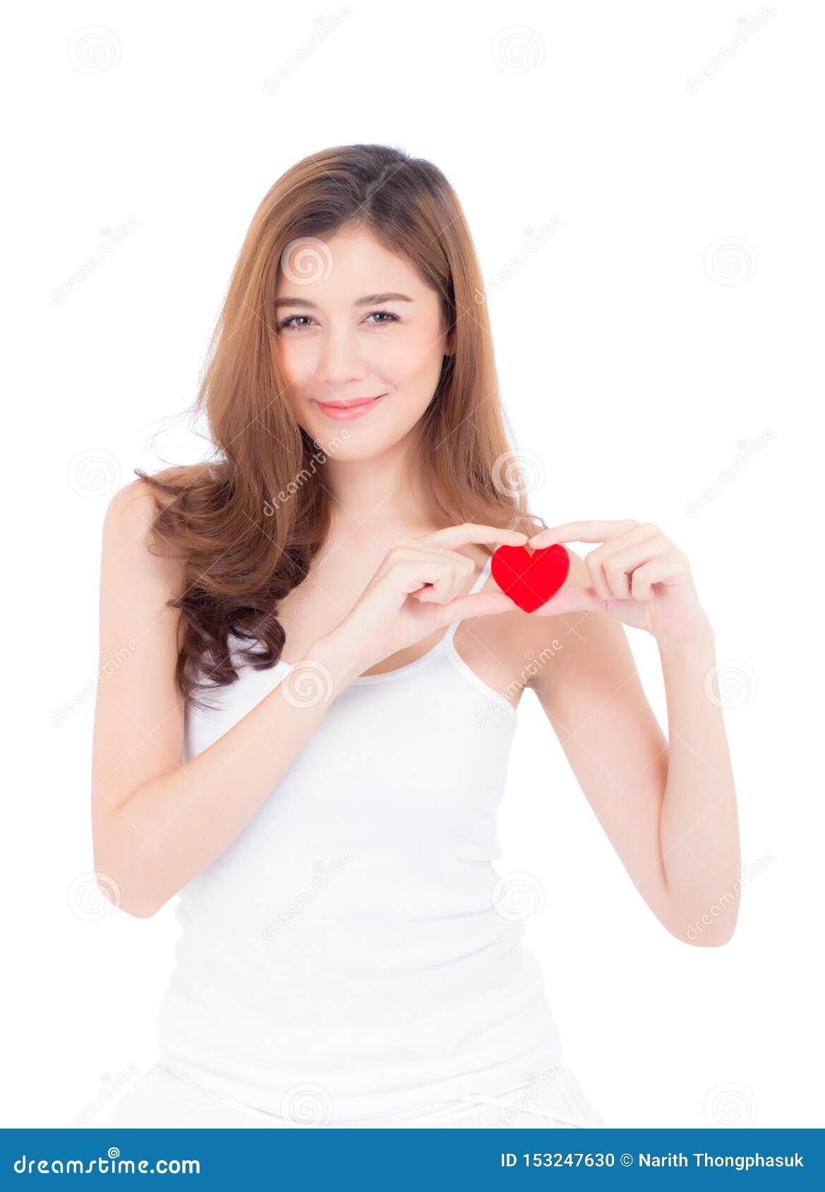 St?ende av den h?rliga asiatiska unga kvinnan som rymmer den r?da hj?rtaformkudden och leende som isoleras p? vit bakgrund