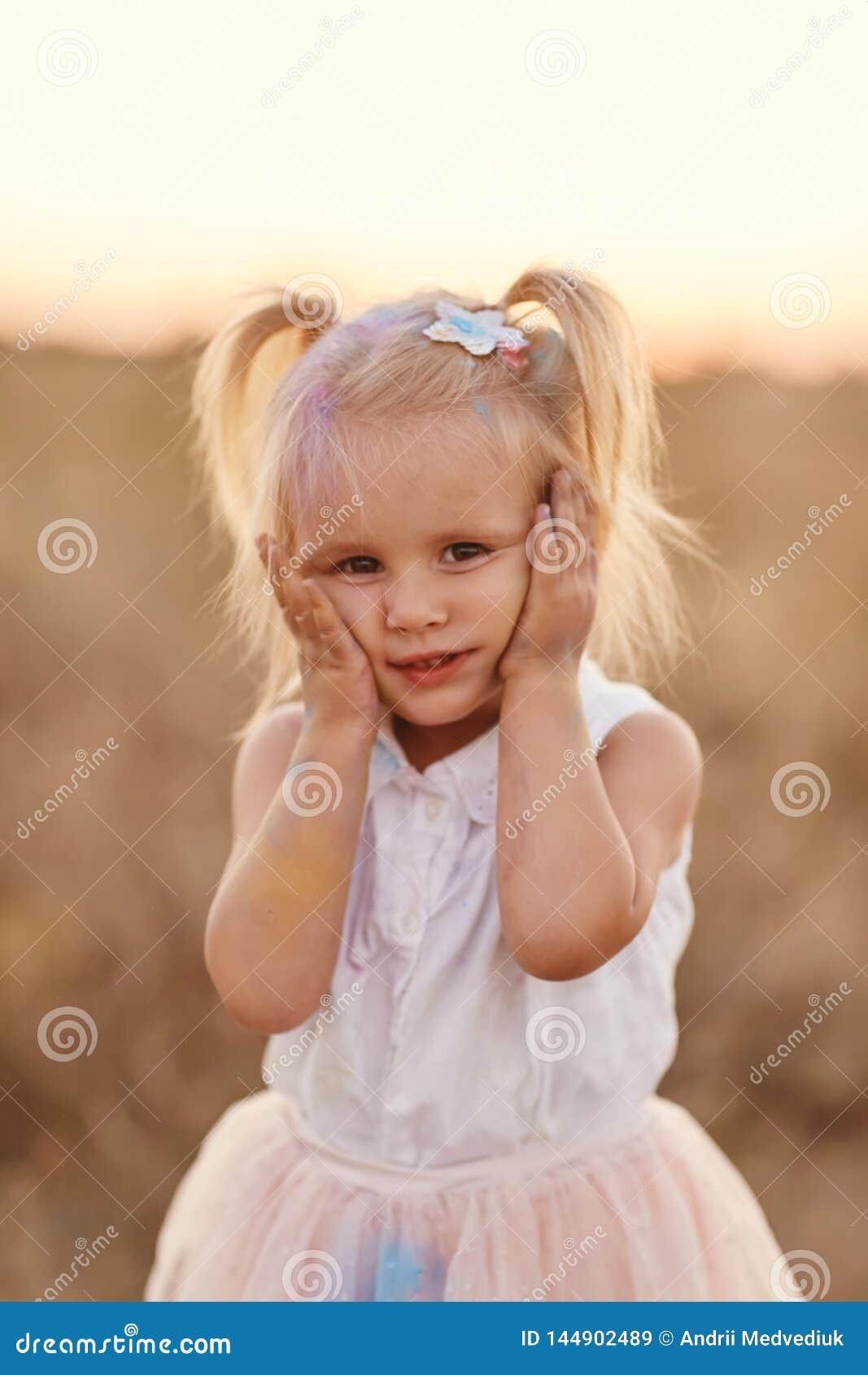 St?ende av den lyckliga flickan suddig med kul?rt pulver Liten flicka med tv? svansar