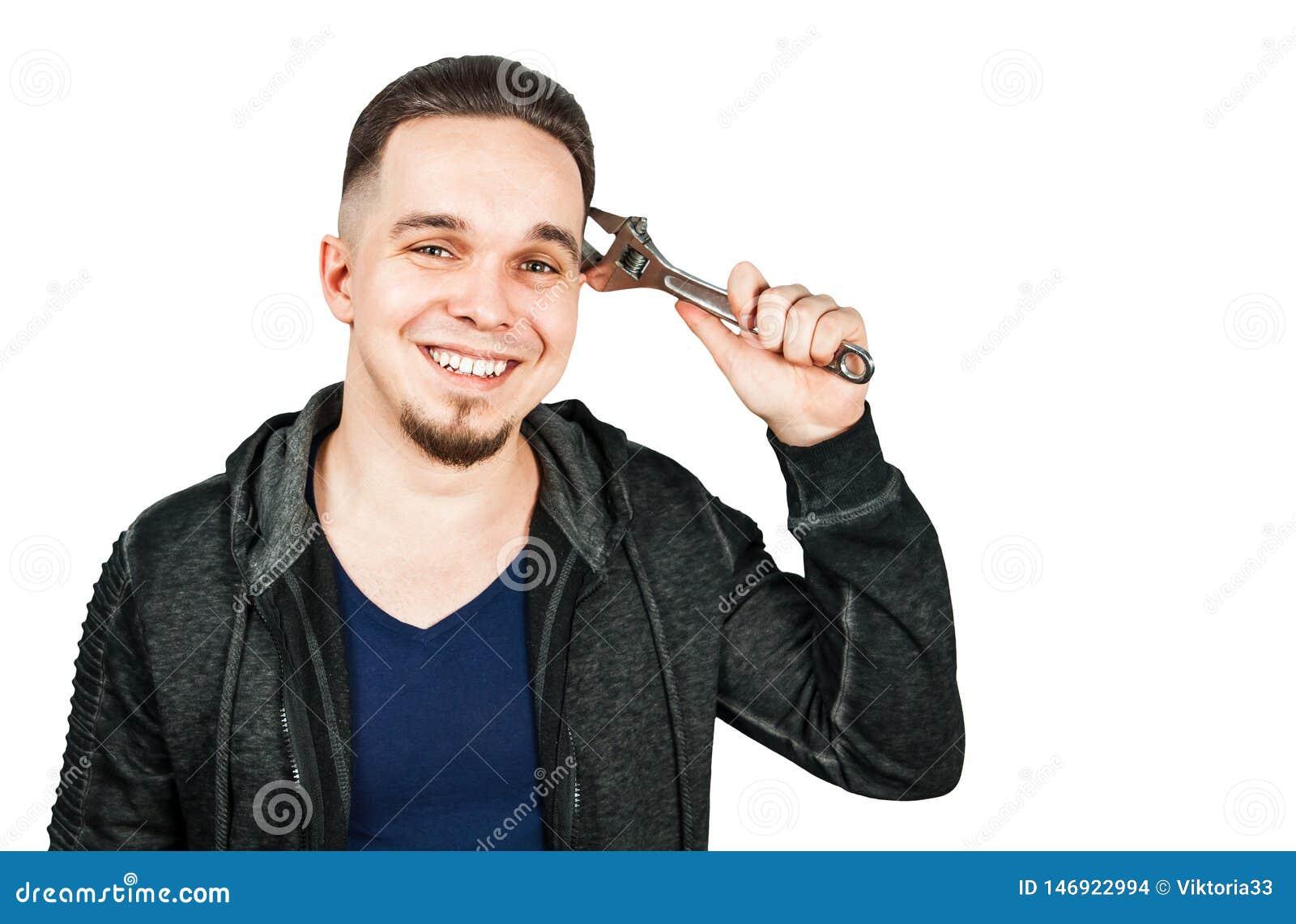 St?ende av den sk?ggiga unga mannen som rymmer den justerbara skiftnyckeln bakgrund isolerad white