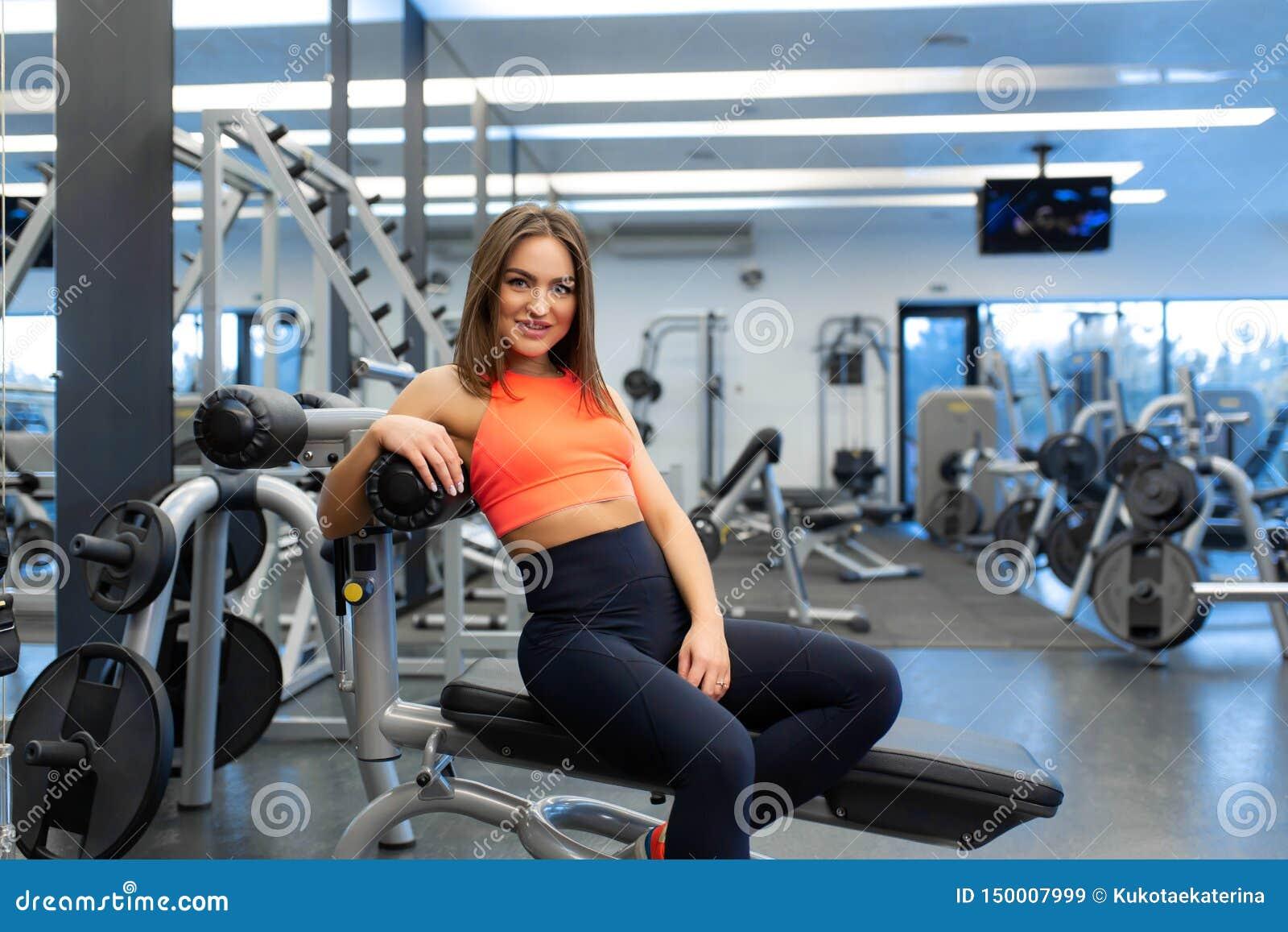 St?ende av den slanka stiliga unga kvinnan att koppla av i idrottshall efter h?rd utbildning