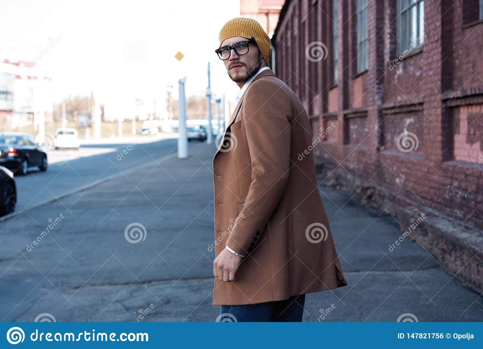 St?ende av den stilfulla stiliga unga mannen i exponeringsglas med borstet som utomhus st?r B?rande omslag och skjorta f?r man