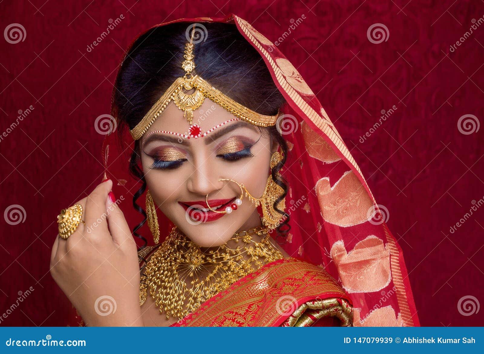 St?ende av den unga indiska bruden som b?r guld- smycken och den r?da sari i br?llop