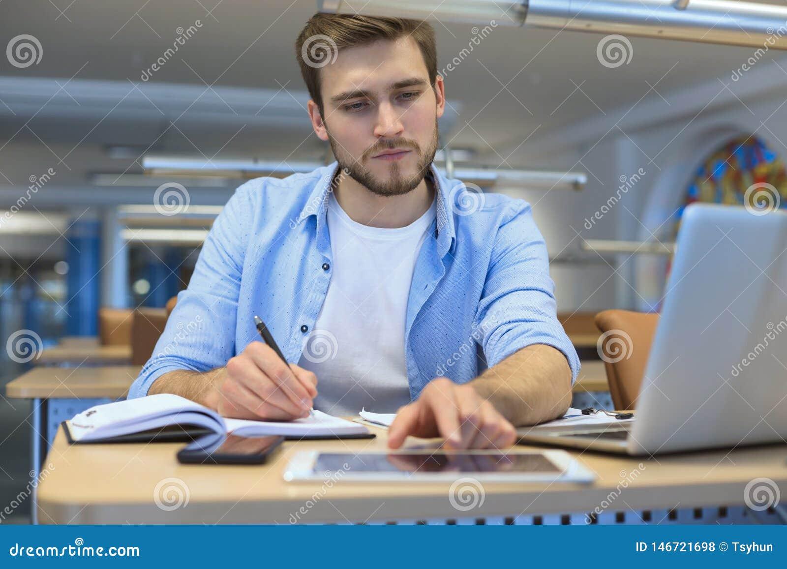 St?ende av sammantr?de f?r ung man p? hans skrivbord i kontoret