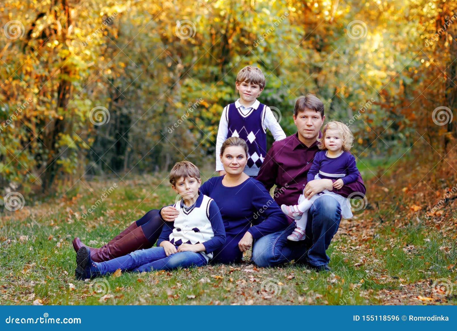 St?ende av unga f?r?ldrar med tre barn Moder, fader, tv? pojkar f?r ungebr?der och liten gullig litet barnsyster