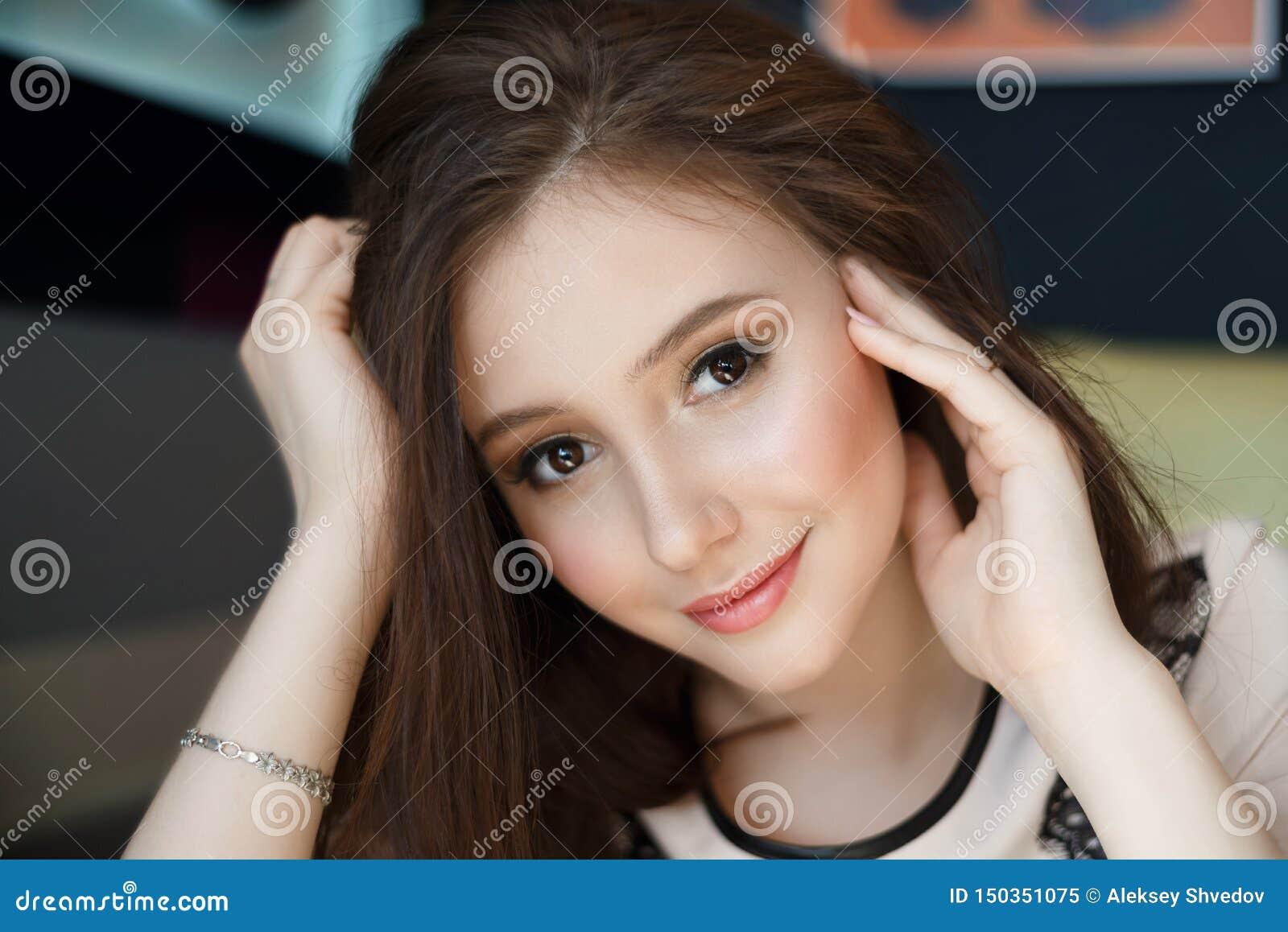 St?ende som charmar den unga kvinnan med v?nligt leende, l?ngt brunetth?r som ler kaf?t