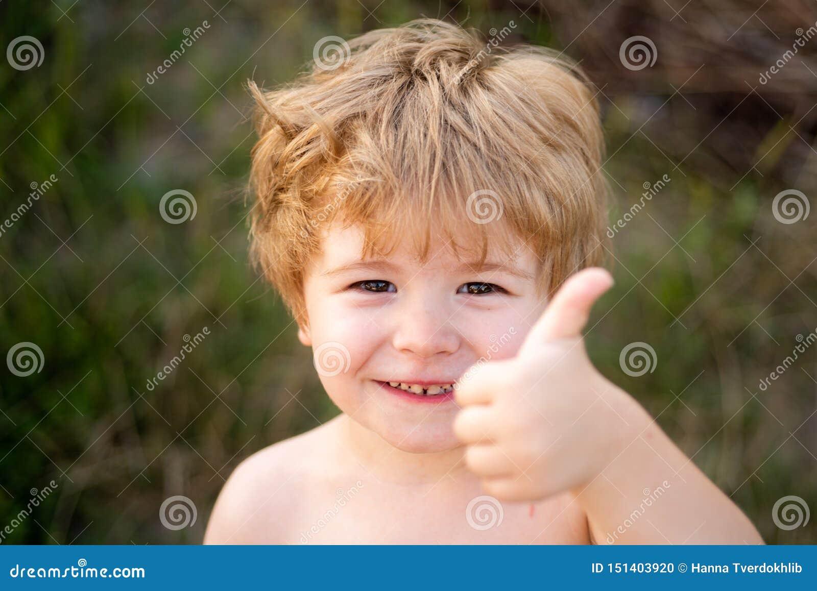 St?enden av lyckliga pojkevisningtummar g?r en gest upp Barn på naturgräsplanbakgrund lycklig din feriesommar f?r familj