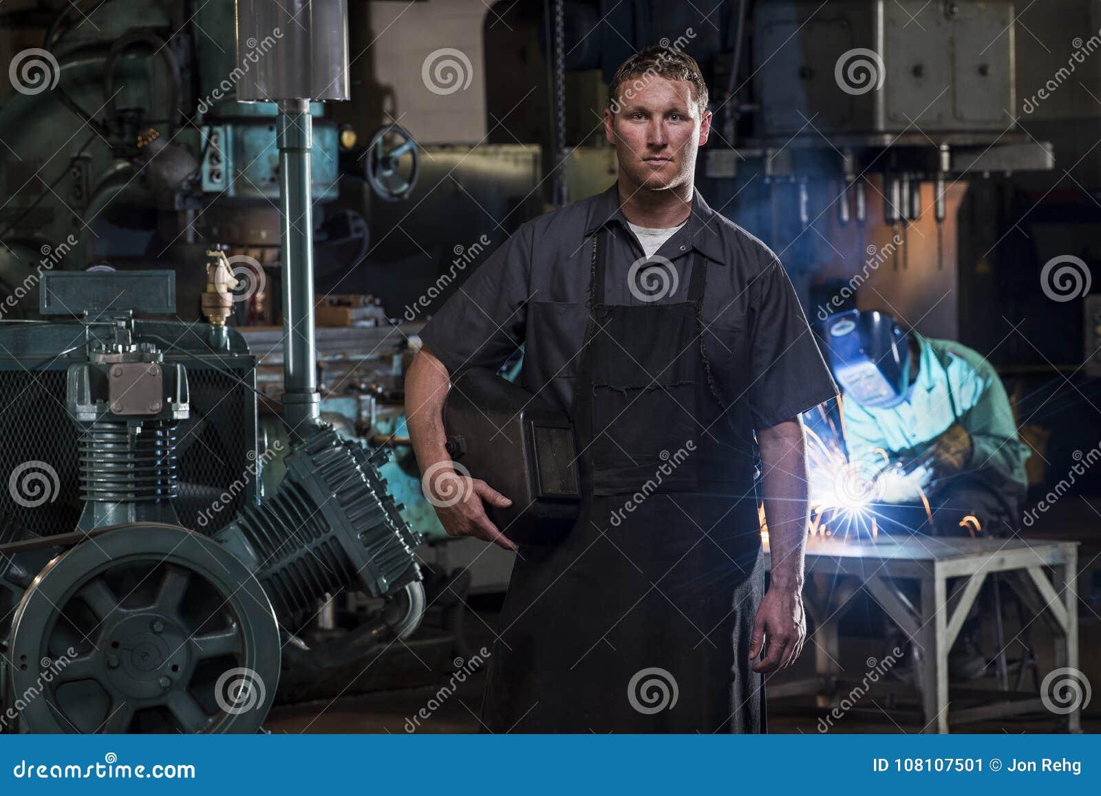St Louis, Missouri, EUA-cerca de 2015-Portrait do soldador masculino com máscara na usina e na solda do homem
