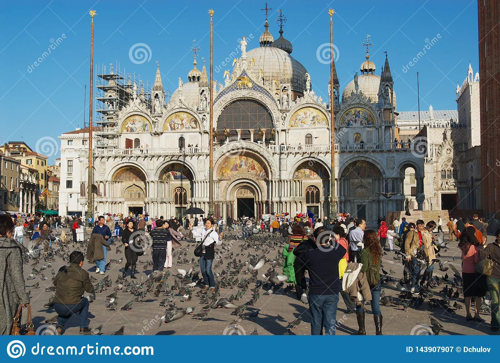 Tourists feed pigeons make photos with Saint Mark Basilica at the background at Piazza San Marco in Venice, Italy.