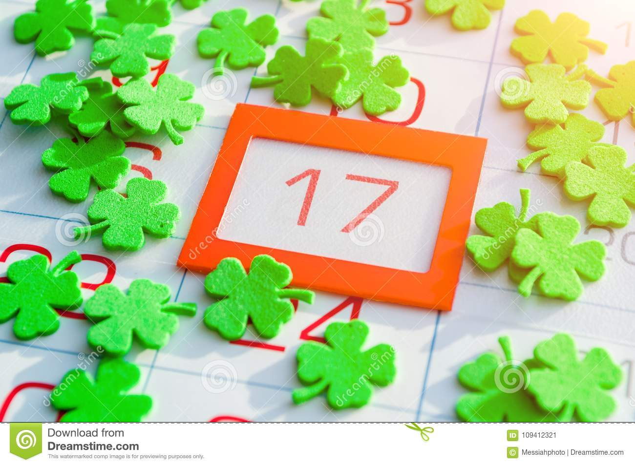 St Patrick`s Day festive background. Green quatrefoils covering the calendar with bright orange framed 17 March