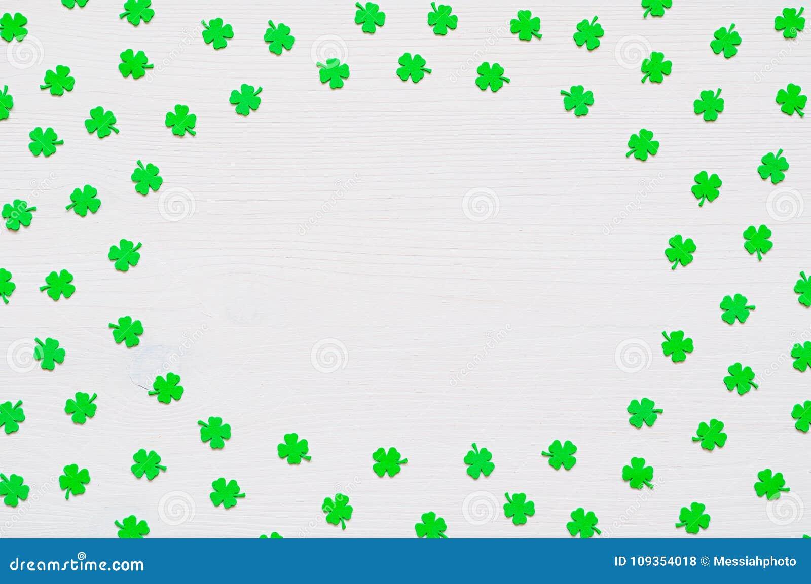 St Patrick`s Day background with green quatrefoils on white background, round border