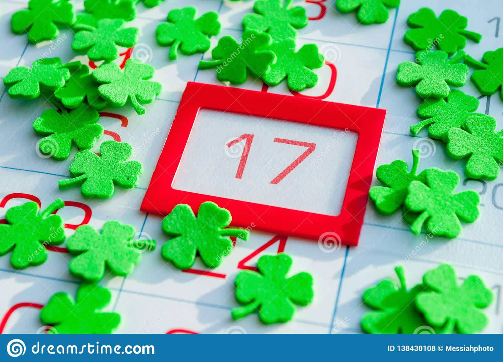 St Patrick`s Day festive background. Green quatrefoils covering the calendar with bright red framed 17 March