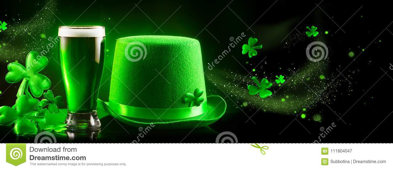 St. Patrick`s Day. Green beer pint and leprechaun hat over dark green background